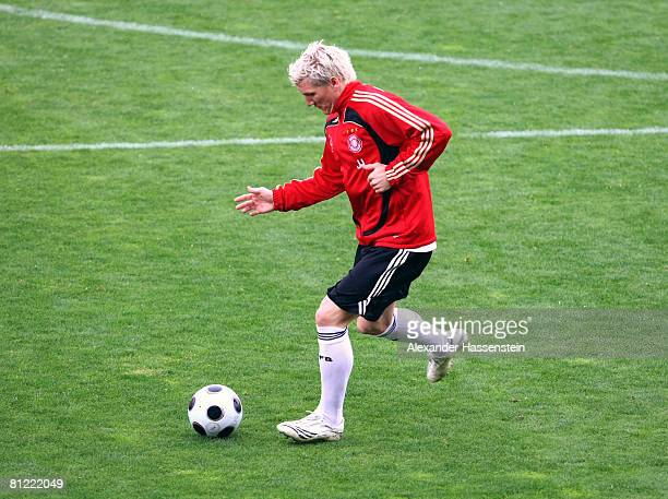 Bastian Schweinsteiger of Germany plays in the training's jacket of his head coach Joachim Loew during a training session at the Son Moix stadium on...