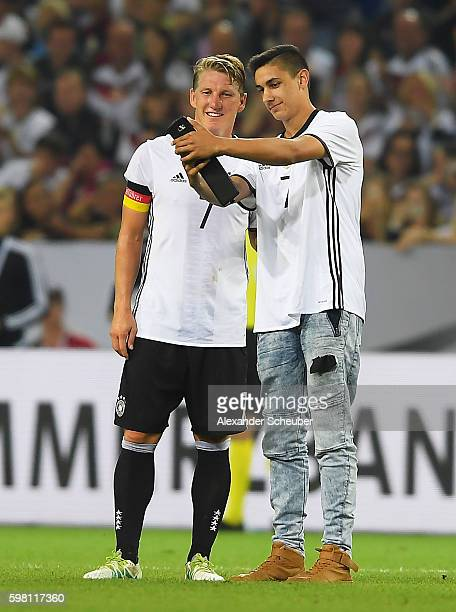 Bastian Schweinsteiger of Germany poses for a photo with a fan during the International Friendly match between Germany and Finland at BorussiaPark on...
