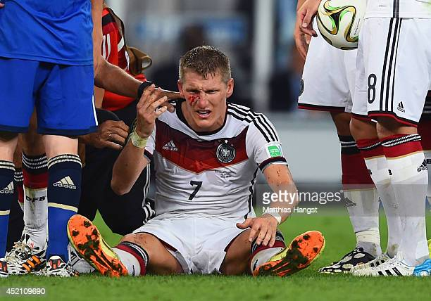 Bastian Schweinsteiger of Germany receives treatment after a collision during the 2014 FIFA World Cup Brazil Final match between Germany and...