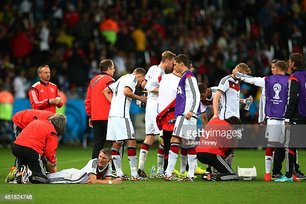 Bastian Schweinsteiger of Germany receives treatment as his teammates take on fluids during the 2014 FIFA World Cup Brazil Round of 16 match between...