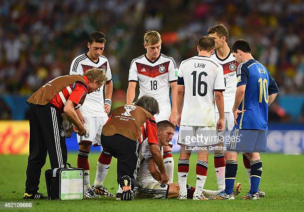 Bastian Schweinsteiger of Germany receives treatment as teammates Mesut Oezil Toni Kroos Philipp Lahm and Thomas Mueller look on with Lionel Messi...