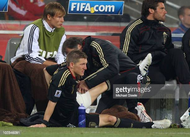 Bastian Schweinsteiger of Germany receives treatment for an injury after being substituted during the 2010 FIFA World Cup South Africa Group D match...