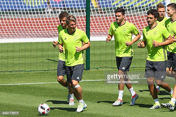 Bastian Schweinsteiger of Germany runs with the team during a Germany training session ahead of their UEFA Euro 2016 Semi final against France at...