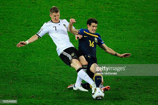 Bastian Schweinsteiger of Germany tackles Carl Valeri of Australia during the 2010 FIFA World Cup South Africa Group D match between Germany and...