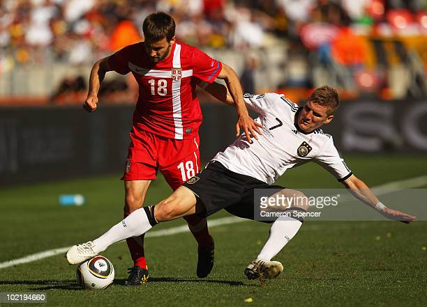 Bastian Schweinsteiger of Germany tackles Milos Ninkovic of Serbia during the 2010 FIFA World Cup South Africa Group D match between Germany and...