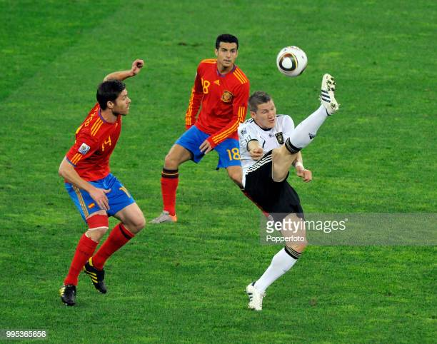 Bastian Schweinsteiger of Germany under pressure from Xabi Alonso and Pedro of Spain during the FIFA World Cup Semi Final at the Moses Mabhida...