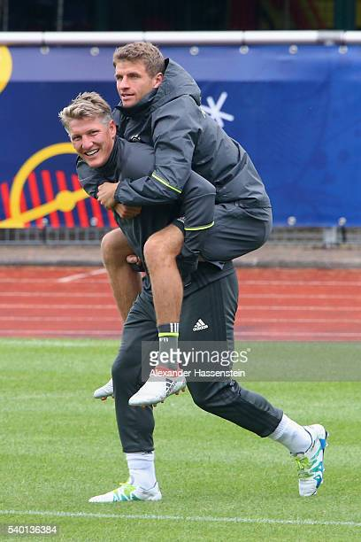 Bastian Schweinsteiger of Germayn jokes with his team mate Thomas Mueller during a Germany training session at Ermitage Evian on June 14 2016 in...