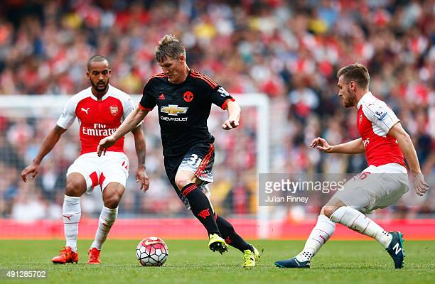 Bastian Schweinsteiger of Manchester United takes on Theo Walcott and Aaron Ramsey of Arsenal during the Barclays Premier League match between...