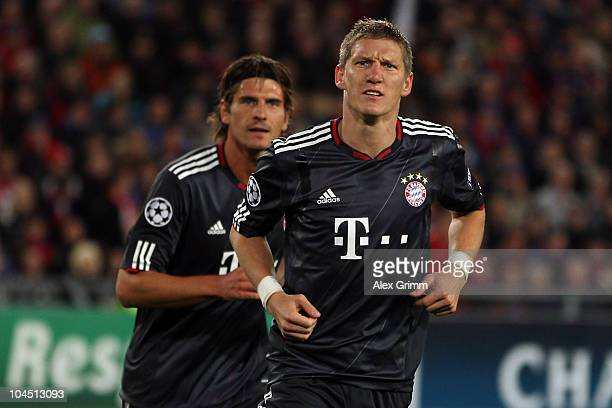 Bastian Schweinsteiger of Muenchen celebrates his team's first goal with team mate Mario Gomez during the UEFA Champions League group E match between...