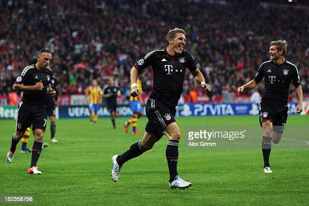 Bastian Schweinsteiger of Muenchen celebrates his team's first goal with team mates Franck Ribery and Toni Kroos during the UEFA Champions League...