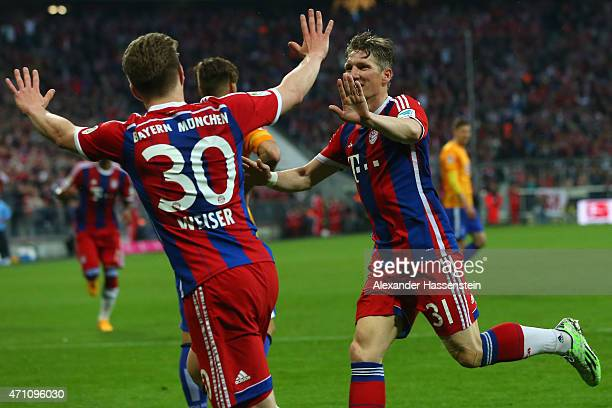 Bastian Schweinsteiger of Muenchen celebrates scoring the opening goal with his team mate Mitchell Weiser during the Bundesliga match between FC...