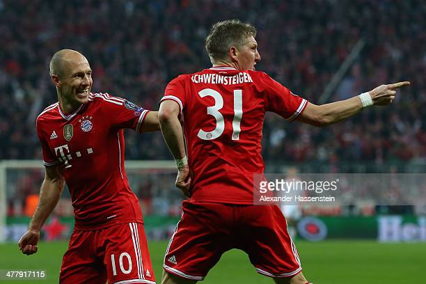 Bastian Schweinsteiger of Muenchen celebrates scoring the opening goal with his team mate Arjen Robben during the UEFA Champions League Round of 16...