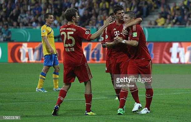 Bastian Schweinsteiger of Muenchen celebrates with team mates after scoring his team's 2nd goal the DFB Cup first round match between Eintracht...