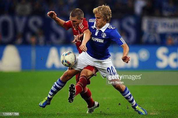 Bastian Schweinsteiger of Muenchen challenges Teemu Pukki of Schalke during the Bundesliga match between FC Schalke 04 and FC Bayern Muenchen at...