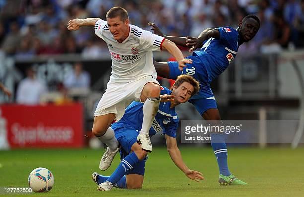Bastian Schweinsteiger of Muenchen is challenged by Dominik Kaiser and Chinedu Obasi of Hoffenheim during the Bundesliga match between 1899...