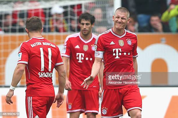 Bastian Schweinsteiger of Muenchen reacts after receiving the first goal during the Bundesliga match between FC Augsburg and FC Bayern Muenchen at...