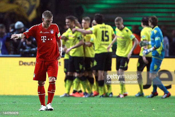 Bastian Schweinsteiger of Muenchen reacts whilst players of Dortmund celebrates their 5th team goal during the DFB Cup final match between Borussia...