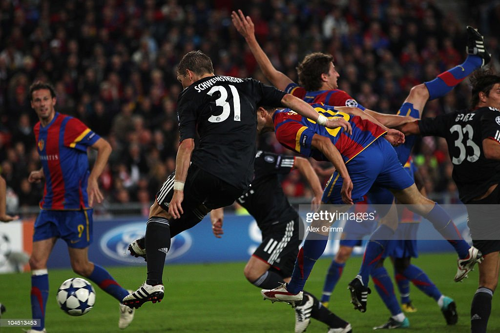 Bastian Schweinsteiger of Muenchen scores his team's second goal against Behrang Safari and Valentin Stocker of Basel during the UEFA Champions League group E match between FC Basel and FC Bayern Muenchen at the St. Jakob Park stadium on September 28, 2010 in Basel, Switzerland.