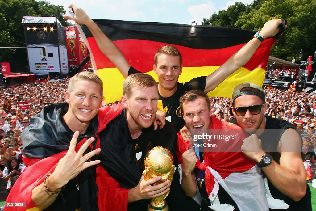 Bastian Schweinsteiger, Per Mertesacker, Manuel Neuer, Kevin Grosskreutz and Lukas Podolski (L-R) celebrate on stage at the German team victory ceremony July 15, 2014 in Berlin, Germany. Germany won the 2014 FIFA World Cup Brazil match against Argentina in Rio de Janeiro on July 13.