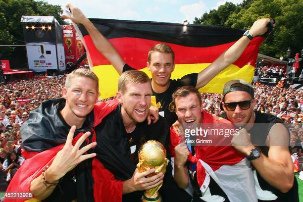 Bastian Schweinsteiger Per Mertesacker Manuel Neuer Kevin Grosskreutz and Lukas Podolski celebrate on stage at the German team victory ceremony July...