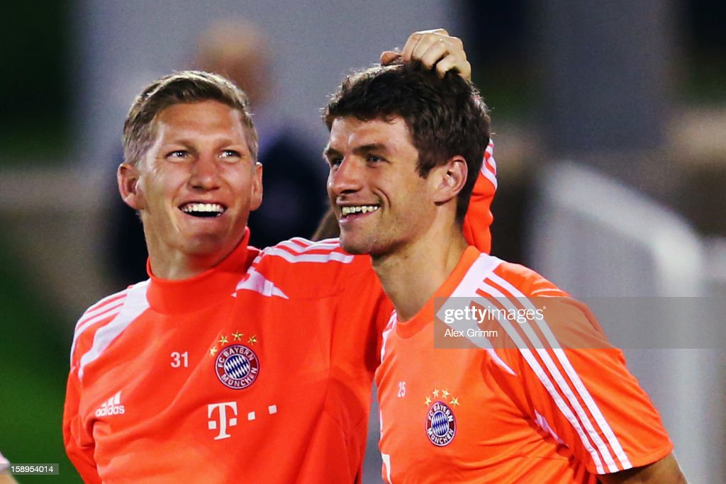 Bastian Schweinsteiger (L) pulls Thomas Mueller's hair during a Bayern Muenchen training session at the ASPIRE Academy for Sports Excellence on January 4, 2013 in Doha, Qatar.