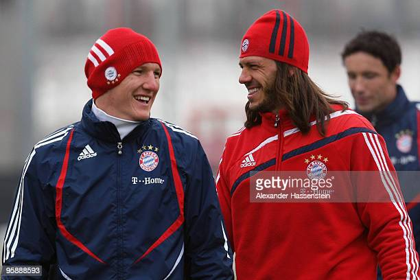 Bastian Schweinsteiger smiles with his team mate Martin Demichelis during the Bayern Muenchen training session at Bayern's training ground 'Saebener...