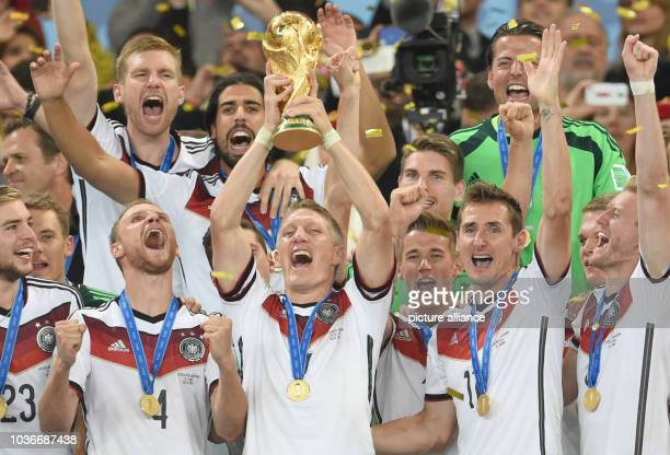 Bastian Schweinsteiger of Germany lifts up the World Cup trophy after winning the FIFA World Cup 2014 final soccer match between Germany and...