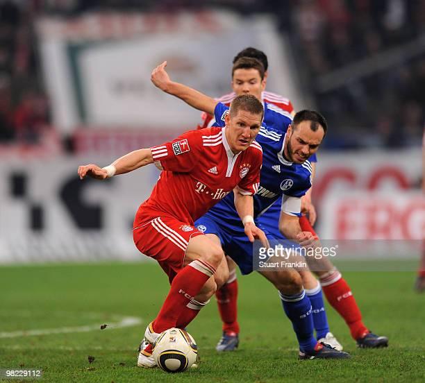 Bastian Schweinstieger of Bayern is challenged by Heiko Westermann of Schalke during the Bundesliga match between FC Schalke 04 and FC Bayern...