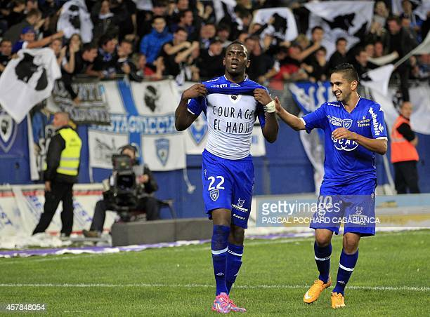 Bastia's French midfielder Christopher Maboulou shows a jersey with the lettering 'courage El Hadji' for Bastia's player ElHadji Ba suffering a...