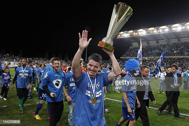 Bastia's French midfielder Yannick Cahuzac celebrates with the L2 trophy after winning the L2 competition following their victory at the enf of the...