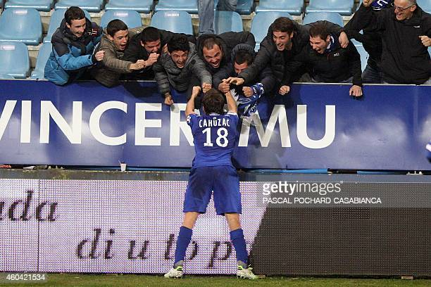 Bastia's French midfielder Yannick Cahuzac is congratulated by supporters after scoring a goal during the French L1 football match Bastia against...