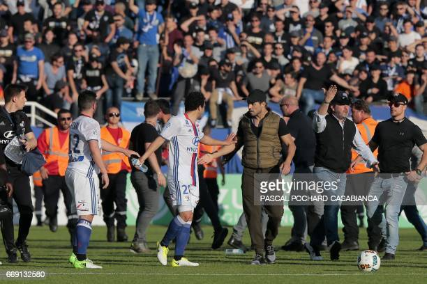 A Bastia's official argues with Lyon's Brazilian defender Rafael da Silva during scuffles at halftime between some of Lyon's players and Bastia's...