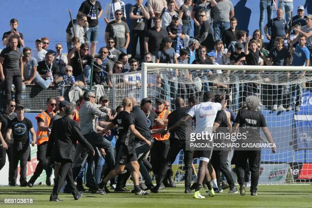 Bastia's supporters invade the pitch and shoot at Lyon players during warm up prior to the French L1 Football match between Bastia and Lyon on April...