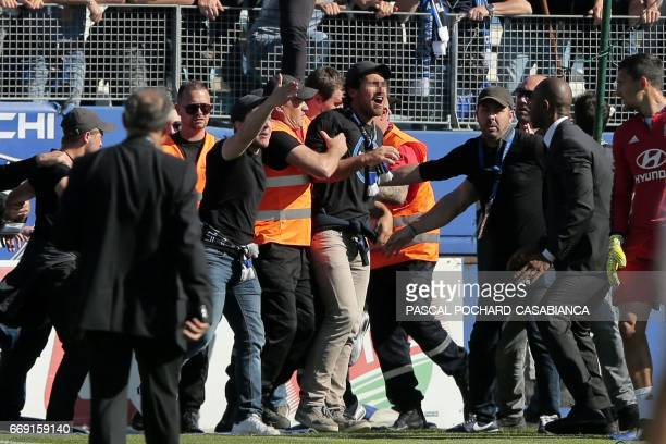 Bastia's supporters invade the pitch to try to fight with Lyon's Portuguese goalkeeper Anthony Lopes and players during their warm up prior to the...
