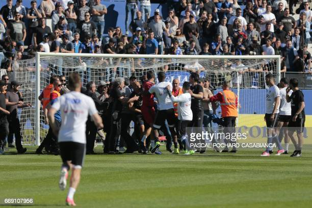 Bastia's supporters invade the pitch try to fight with Lyon players during warm up prior to the French L1 Football match between Bastia and Lyon on...