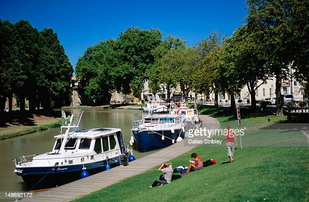 bastide st louis (carcassonnes's new town _ ,backpackers enjoying grassy banks of canal du midi. - guy carcassonne stock pictures, royalty-free photos & images