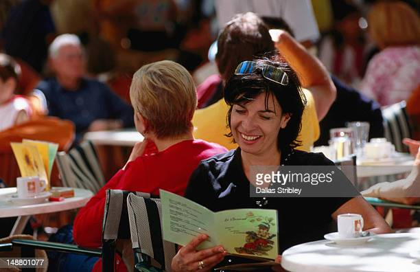 Bastide St Louis (Carcassonne's new town ), woman reading menu at outdoor cafe in Place Carnot.