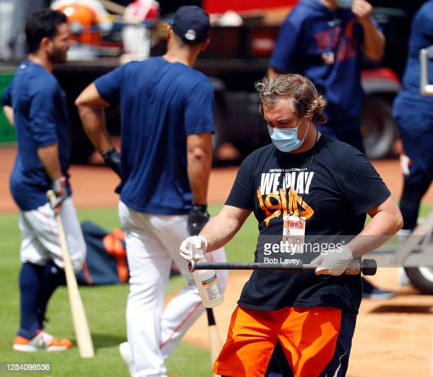 Bat boy Chase Wornell disinfects a warm up bat during batting practice during the first day of Summer workouts for the Houston Astros at Minute Maid...