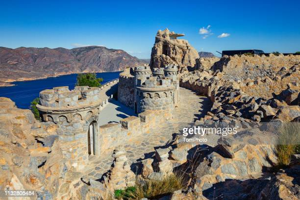 bateria de castillitos - the watchman battery, fortified building with crenelated towers and stone walls in the mountains on the seacoast. cartagena, murcia, spain - lugar histórico - fotografias e filmes do acervo