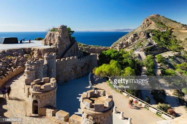 bateria de castillitos - the watchman battery, fortified building with crenelated towers and stone walls in the mountains on the seacoast. cartagena, murcia, spain - murcia - fotografias e filmes do acervo