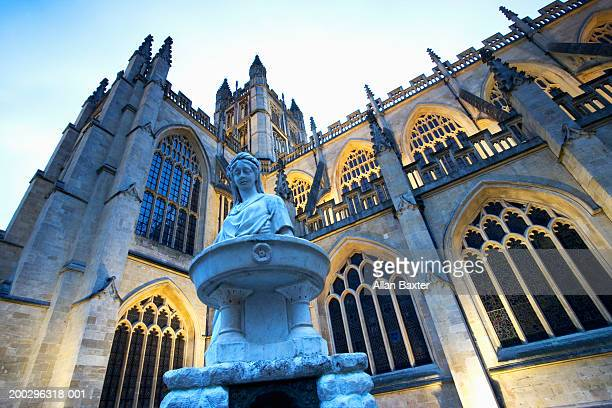 Bath Abbey illuminated exterior and marble statue, low angle view