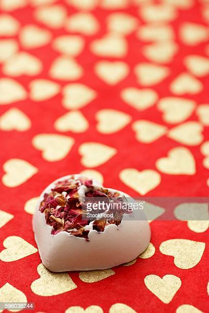Bath bomb with rose petals on a red background patterned with hearts