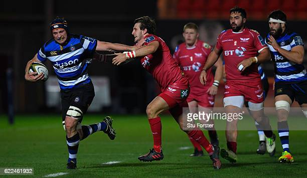 Bath number 8 Paul Grant charges away from the tackle of Dan Jones of Scarlets during the AngloWelsh Cup match between Scarlets and Bath at Parc y...