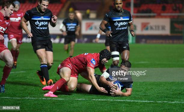 Bath player Rhys Priestland has his slide towards the line stopped by Leigh Halfpenny during the European Rugby Champions Cup match between Scarlets...