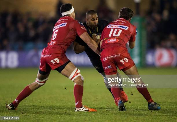 Bath Rugby's Aled Brew is tackled by Scarlets Aaron Shingler and Dan Jones during the European Rugby Champions Cup match between Bath Rugby and...