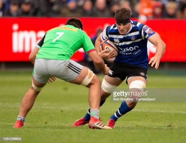 Bath Rugby's Josh Bayliss evades the tackle of Harlequins' Archie White during the Premiership Rugby Cup match between Bath Rugby and Harlequins at...