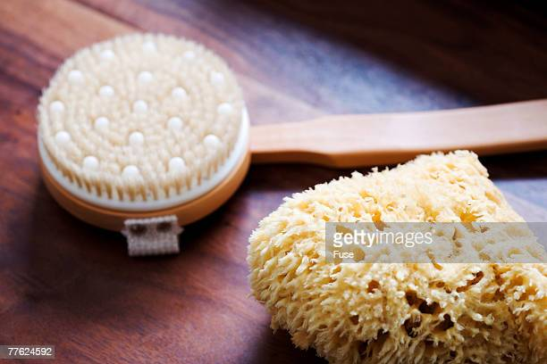 a bath scrub brush and natural sea sponge on a wooden table - loofah stock photos and pictures