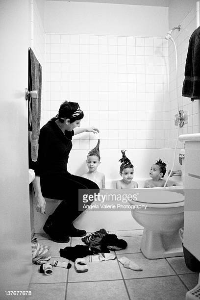 bath time - girl sitting on boys face stock photos and pictures
