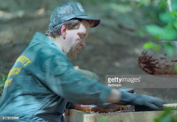 A member of the investigating team searching the yard of the former home of confessed mass murderer Jeffrey Dahmer sifts through dirt looking for...