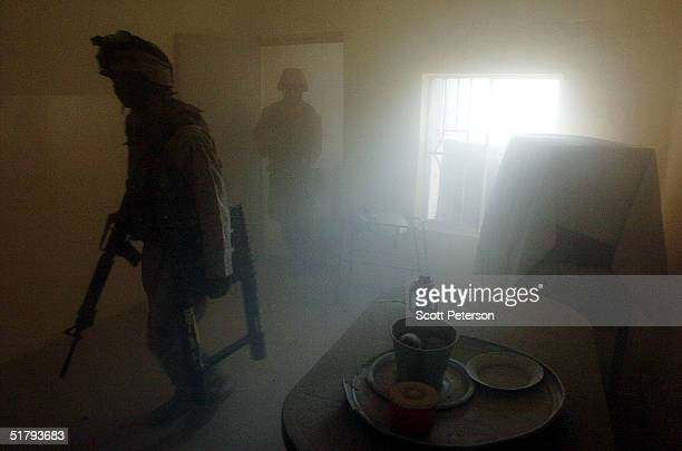 Bathed in the smoke of their own grenades US Marines of the 1st Light Armored Reconnaissance company as part of 1st Battalion 3rd Marines clear and...